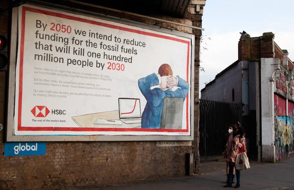 A passer-by looks at a spoof HSBC billboard advert